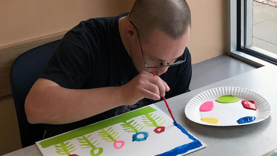 A man painting flowers