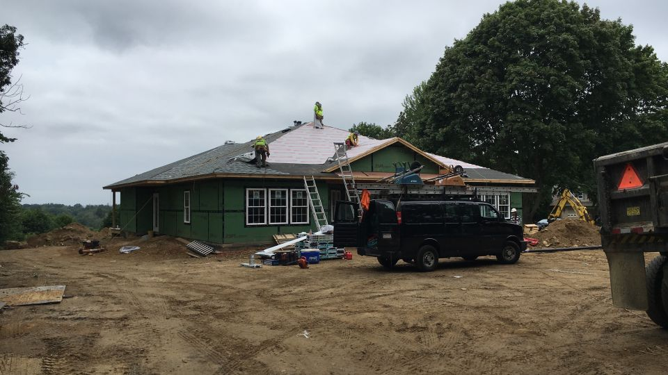 Front view of house with roof nearly complete.