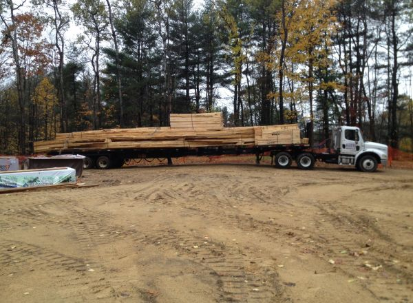 Truck rolls in with the roof trusses and other supplies.