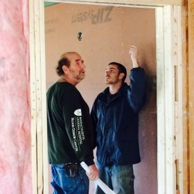 Construction Manager John Smith discusses details of the safe room with a contractor.